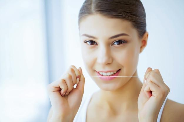 Hermosa mujer joven con dientes blancos limpia los dientes con hilo dental
