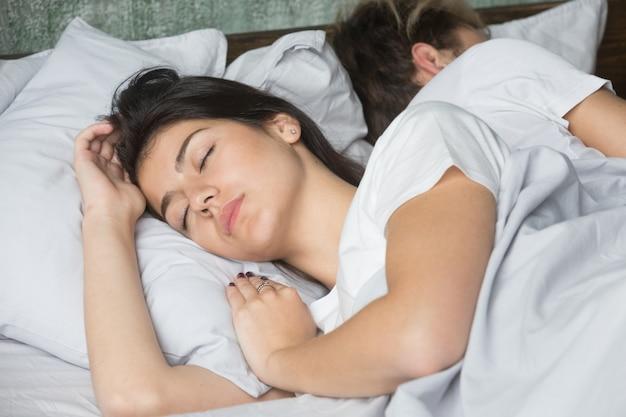 Hermosa mujer joven durmiendo cómodamente en una cama acogedora con su novio