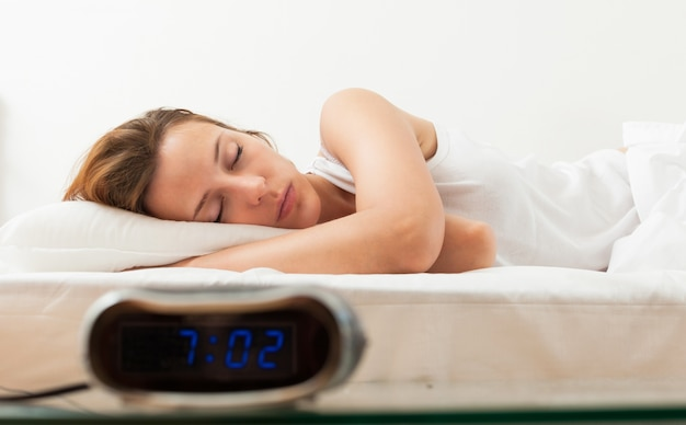 Hermosa mujer joven durmiendo en malos con despertador