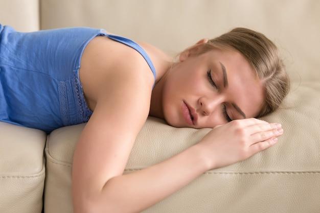 Hermosa mujer joven durmiendo en el sofá en casa, retrato en la cabeza
