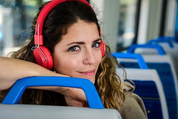 Hermosa mujer joven escuchando música en un tren.