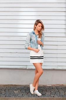 Hermosa mujer joven con estilo en ropa de verano de moda posando en la calle cerca de una casa blanca de madera. chica moderna. ropa de estilo americano.