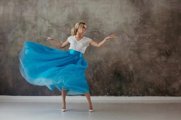 Hermosa mujer joven en una exuberante falda azul, girando y bailando.