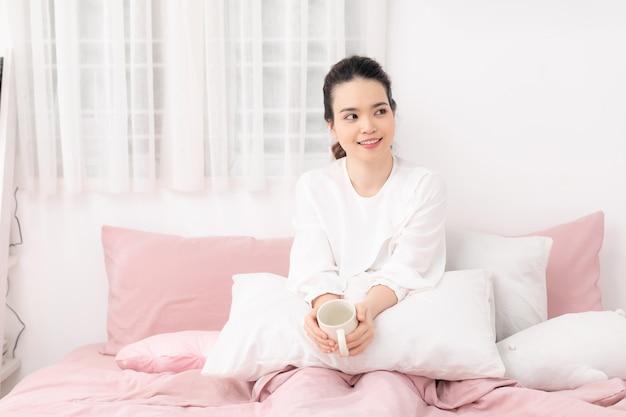 Hermosa mujer joven feliz bebiendo una taza de café o té mientras está acostado en la cama después de despertarse por la mañana.