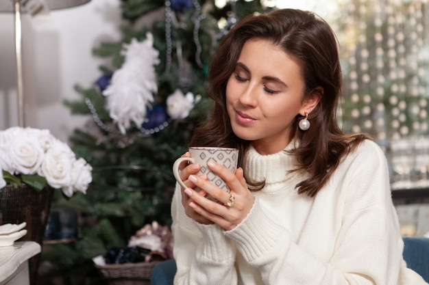 Hermosa mujer joven feliz en casa para navidad