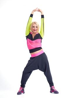 Hermosa mujer joven feliz con labios rojos en ropa deportiva bailando alegremente en blanco