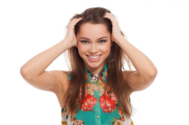 Hermosa mujer joven feliz sosteniendo su cabeza