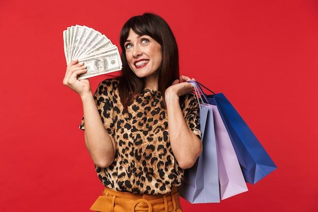 Hermosa mujer joven feliz vestida con camisa estampada de animales posando aislada sobre pared roja con dinero y bolsas de la compra.