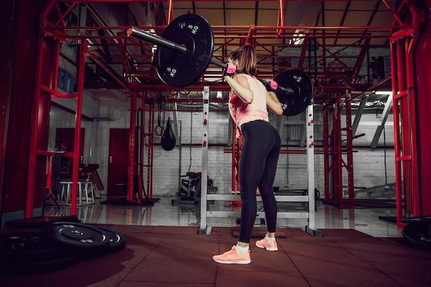 Hermosa mujer joven fitness agacharse y hacer ejercicio de escuadrón con una barra detrás del cuello en el gimnasio.