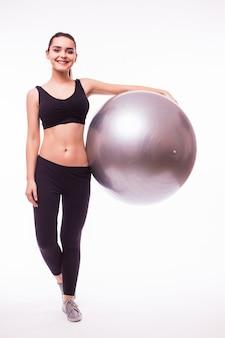 Hermosa mujer joven fitness con ejercicio de pelota de gimnasia, aislado sobre fondo blanco.