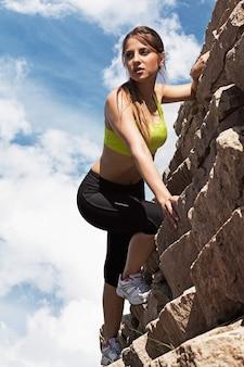 Hermosa mujer joven en fitwear escalada