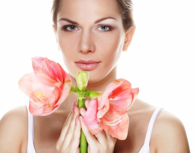 Hermosa mujer joven con flor rosa sobre blanco