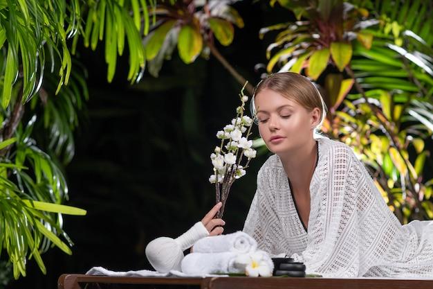 Hermosa mujer joven con flores blancas con bata de baño acostado en la mesa de masaje en un tropical