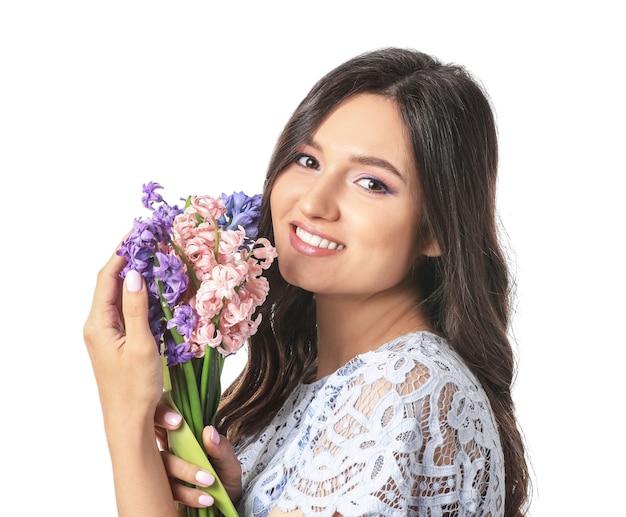 Hermosa mujer joven con flores de jacinto en blanco