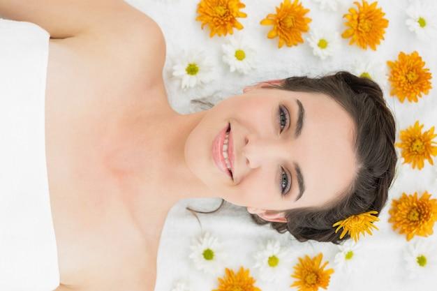 Hermosa mujer joven con flores en el salón de belleza