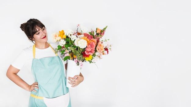 Hermosa mujer joven con flores sobre fondo blanco