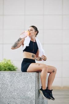 Hermosa mujer joven en forma descansando sobre el parapeto y bebiendo agua dulce después de agotar el entrenamiento al aire libre