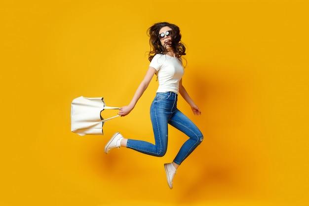 Hermosa mujer joven en gafas de sol, camisa blanca, blue jeans saltando con bolsa sobre el fondo amarillo