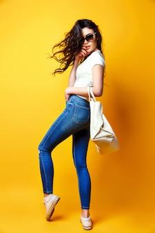 Hermosa mujer joven en gafas de sol, camisa blanca, jeans azul posando con bolsa