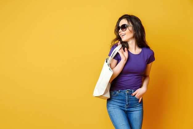 Hermosa mujer joven en gafas de sol, camisa morada, blue jeans posando con bolsa sobre fondo amarillo