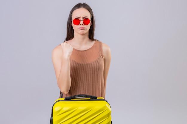 Hermosa mujer joven con gafas de sol rojas de pie con maleta de viaje levantando el puño con expresión de enojo en la cara de pie sobre fondo blanco.