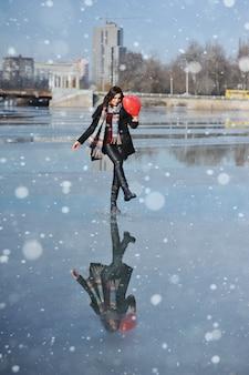 Hermosa mujer joven con un globo en forma de corazón en un río congelado