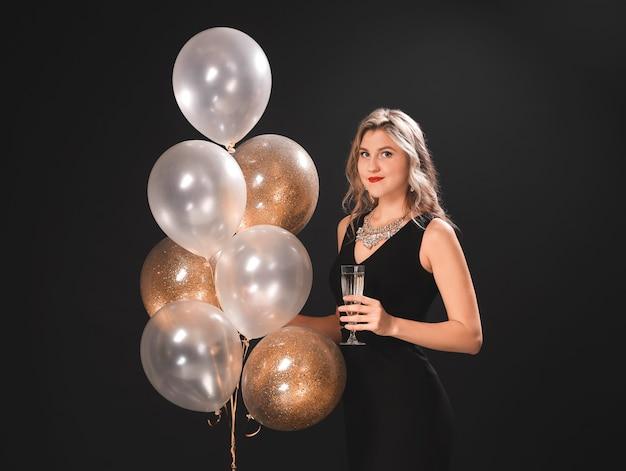 Hermosa mujer joven con globos y champán en superficie oscura