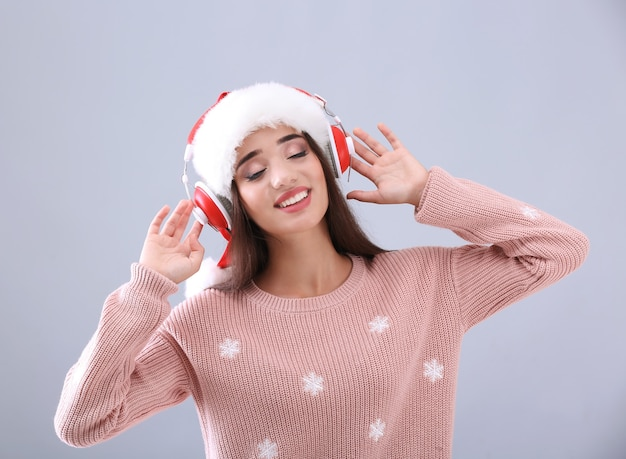 Hermosa mujer joven con gorro de papá noel escuchando música navideña en gris