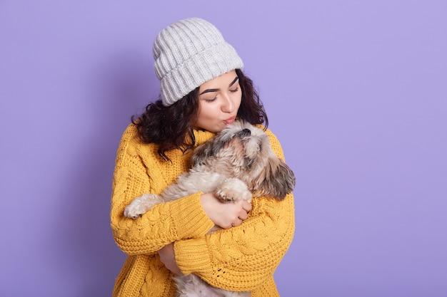 Hermosa mujer joven con gracioso perro pequinés en espacio lila
