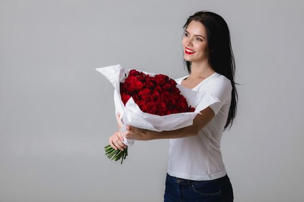Hermosa mujer joven con un gran ramo de rosas rojas