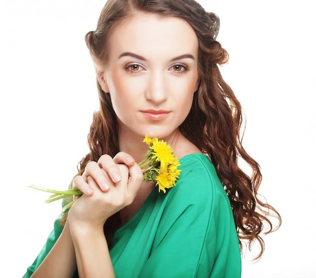 Hermosa mujer joven con grandes dientes de león amarillos