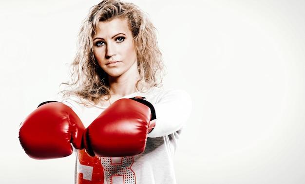 Hermosa mujer joven en guantes de boxeo sobre fondo blanco.