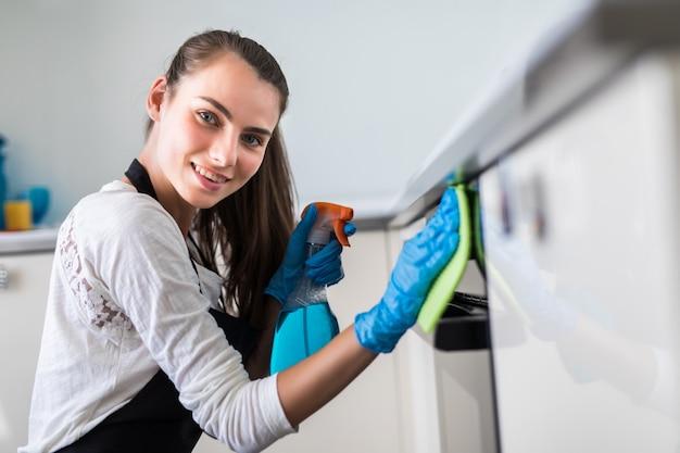 Hermosa mujer joven en guantes protectores de limpieza del horno con un trapo