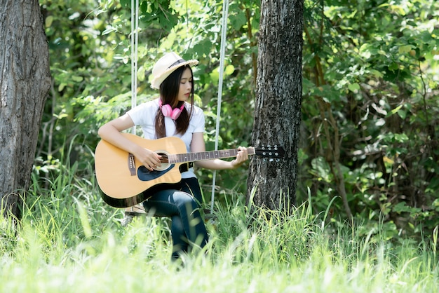 Hermosa mujer joven con guitarra acústica en la naturaleza