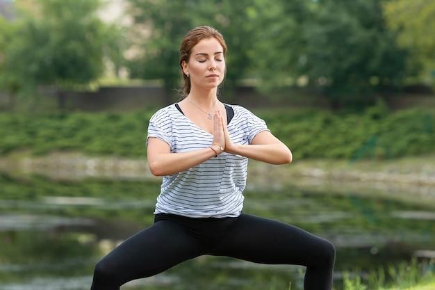 Hermosa mujer joven haciendo ejercicio de yoga en el parque verde
