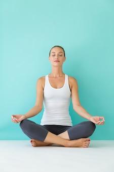 Hermosa mujer joven haciendo yoga en casa.