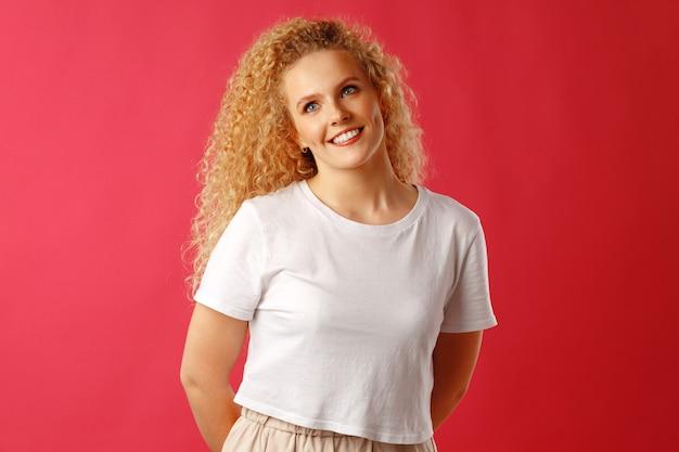 Hermosa mujer joven hermosa con el pelo rizado posando en la cámara de cerca
