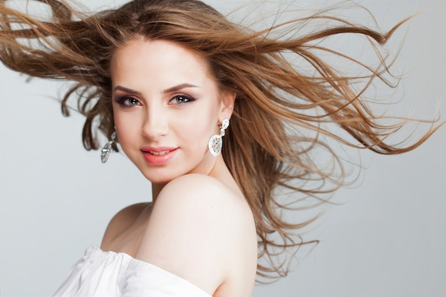 Hermosa mujer joven con hermosos aretes, retrato de primer plano. cabello volador