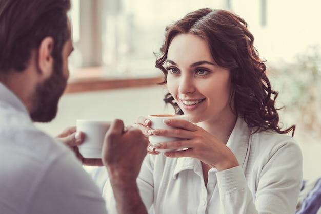 Hermosa mujer joven y hombre enamorado están bebiendo café.