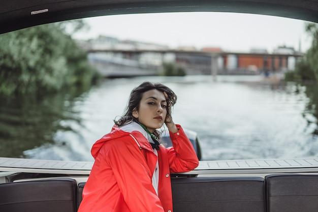 Hermosa mujer joven en un impermeable rojo monta un yate privado. estocolmo, suiza