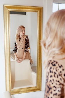 Hermosa mujer joven inteligente de pie delante de un espejo. niña sonriente caucásica mirando reflejo en el espejo
