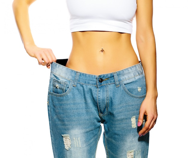 Hermosa mujer joven con jeans grandes, aislado en blanco