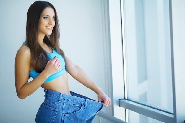 Hermosa mujer joven con jeans grandes y cinta métrica