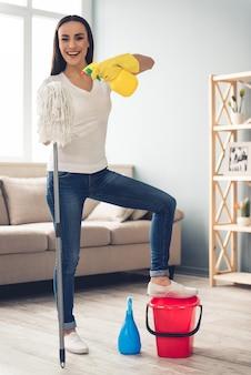 Hermosa mujer joven en jeans está sosteniendo una fregona. concepto de limpieza