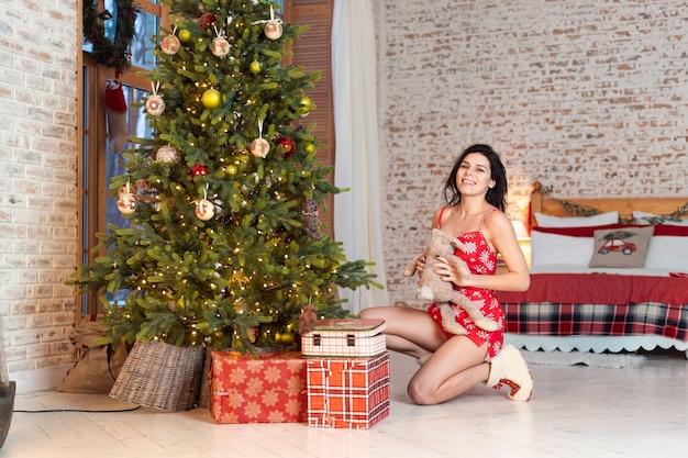 Hermosa mujer joven jugando con un oso de peluche junto al árbol de navidad