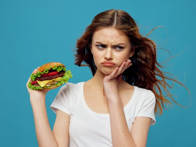 Hermosa mujer joven con una jugosa hamburguesa en sus manos, una mujer comiendo una hamburguesa