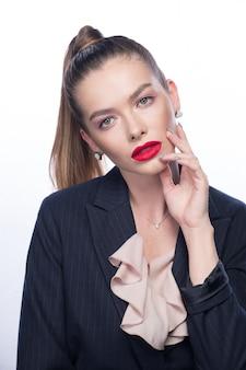 Hermosa mujer joven con labios rojos y cola alta en blanco brillante