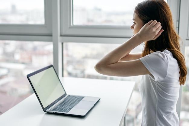 Hermosa mujer joven con laptop en camiseta blanca