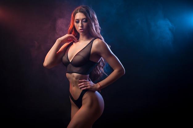 Hermosa mujer joven en lencería negra posando