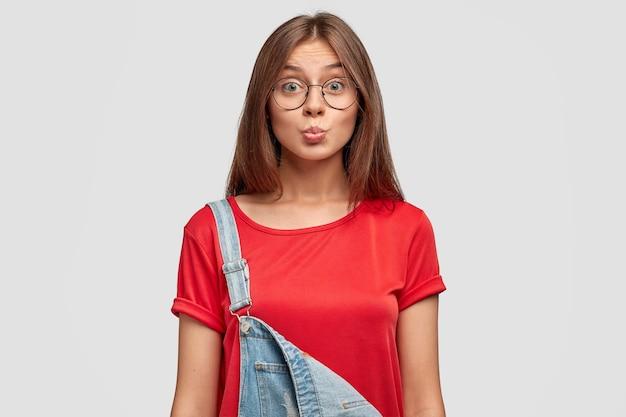 Hermosa mujer joven linda con expresión amistosa, hace muecas, hace pucheros en los labios, vestida con una elegante camiseta roja y un mono, posa contra la pared blanca. adorable estudiante listo para caminar afuera